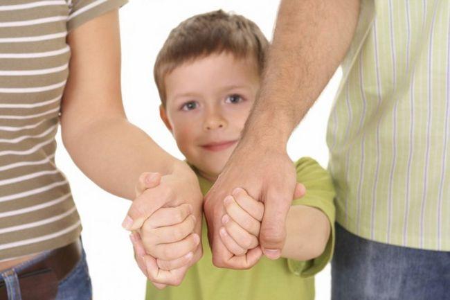 дитина тримає батьків за руки
