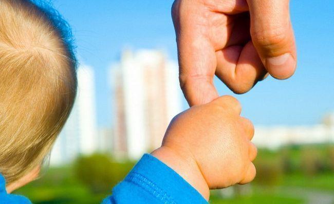 дитина тримає батька за палець