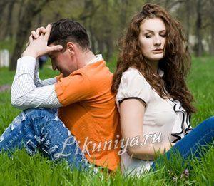 Чоловік і жінка сидять на траві спиною один до одного